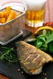 Bakad dorado med nya sallad och grönsaker Blåttskyen, stillhet bevattnar Arkivbild