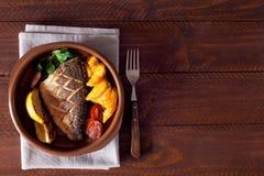 Bakad dorado med nya sallad och grönsaker Top beskådar Brun trätabell Royaltyfri Bild