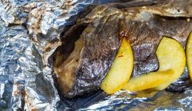 Bakad fisk i folie med citronen och äpplen utomhus Royaltyfri Fotografi