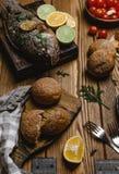 Bakad fisk med citronen och örter på träbräde med bröd och tomater Arkivfoton