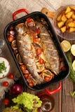 Bakad fisk med grönsaker och potatisar i panna Arkivfoton