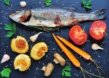 Bakad fisk med grönsaker på en svart bakgrund Royaltyfria Foton