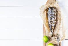 Bakad fisk med limefrukt på pergamentpapper och skärbrädan på en vit bakgrund av den gamla horizonten för bästa sikt för träbräde fotografering för bildbyråer