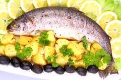 Bakad fisk med potatisar, svart oliv, sallad och citronen Royaltyfri Fotografi