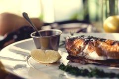 Bakad fisk med rosmarin, sås och citronen på a Arkivbilder