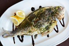 Bakad fisk med sås och citronen Royaltyfri Fotografi