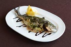 Bakad fisk med sås och citronen Arkivbild
