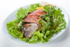 Bakad fisk och bacon med grönsallat och citronen. på a  Royaltyfri Bild