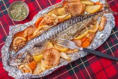 Bakad fisk på en bordduk Arkivfoton