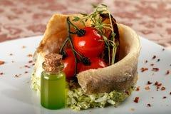 Bakad fisk på en grönsaksidomaträtt med körsbärsröda tomater Royaltyfria Bilder