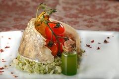 Bakad fisk på en grönsaksidomaträtt med körsbärsröda tomater Royaltyfri Foto