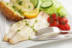 Bakad fiskfilé, tomater, potatis och sallad Arkivbilder