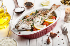 Bakad fiskforell med grönsaker arkivfoto