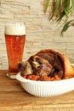 Bakad grisköttlägg med surkålen och öl Fotografering för Bildbyråer