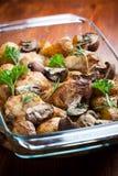 Bakad höna på potatisar och champinjoner Arkivfoton