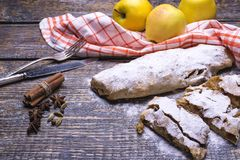 Bakad hemlagad äpplestrudel för sötsak nytt med sockerpulver och rå gula äpplen på en träbakgrund arkivbild