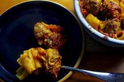 Bakad köttbullepasta på en svart platta med en pasta fyllde eldfasta formen Royaltyfri Foto