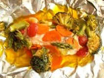 Bakad lax med grönsaker i aluminum folie Arkivbilder