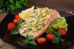 Bakad lax med ost och mandeln, med mosade potatisar och gröna ärtor Fotografering för Bildbyråer