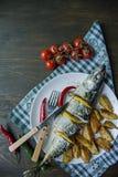 Bakad makrill med citronen och bakade potatisar p? en vit platta ?kerbruka produktgr?nsaker f?r ny marknad K?rsb?r chilipeppar be royaltyfria foton