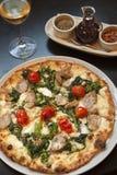 Bakad paesanapizza med ett exponeringsglas av vin Royaltyfria Bilder