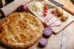 Bakad pizzacalzone med skinka och potatisar och ingredienser traditionell matitalienare Arkivbilder