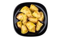 Bakad potatis i den svarta glass plattan som isoleras på vit Arkivfoto
