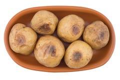 Bakad potatis i en brun platta som isoleras på vit Arkivbilder