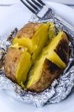Bakad potatis i en folie arkivbilder