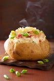 Bakad potatis i omslag med bacon och ost Arkivfoto