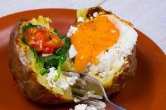 Bakad potatis med den stekte ägg-, feta-, spenat- och tomatkörsbäret royaltyfria bilder