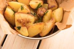 Bakad potatis med vitlök i en panna Arkivfoto