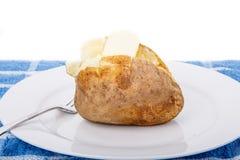Bakad potatis på den vita plattan och blåtthandduken med smör Royaltyfri Foto