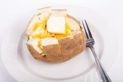 Bakad potatis på plattan med smör och ost Fotografering för Bildbyråer