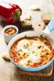 Bakade ägg med tomater och örter Arkivbild