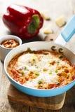 Bakade ägg med tomater och örter Arkivfoton