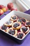 Bakade äpplen med bär och pudrat socker arkivfoto