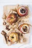 Bakade äpplen med kanelbruna pinnar och hasselnötter på pergamentpapper på skärbräda på en vit bakgrund av det gamla träbrädet fotografering för bildbyråer