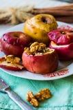 Bakade äpplen med valnötter, honung och kanel, efterrätt Arkivfoton