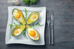 Bakade avokadon med ägg på tabellen fotografering för bildbyråer