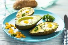 Bakade avokadon med ägg på tabellen royaltyfria bilder