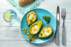 Bakade avokadon med ägg på tabellen arkivfoto