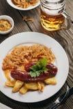 Bakade bayerska korvar med kokt kål och ett exponeringsglas av öl Royaltyfri Foto
