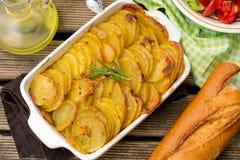 Bakade frasiga potatisskivor med rosmarin tjänade som med sallad Royaltyfria Bilder