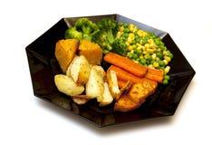 bakade grönsaker för svart platta Royaltyfri Foto