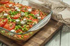 Bakade grönsaker med vit ost och klippt grönska i en glass maträtt på en träyttersida Royaltyfria Bilder