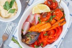 Bakade grönsaker: morötter, rädisor, lökar, tomater och peppar Arkivbilder