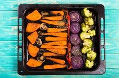 Bakade grönsaker på magasinet på blå träbakgrund arkivbild