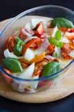 Bakade grönsaker: tomat lök, peppar i bunke. Royaltyfri Bild
