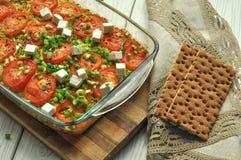 Bakade grönsaker - zucchini, morötter och tomater - med vit ost och klippt grönska i en glass maträtt på en träyttersida Royaltyfri Foto